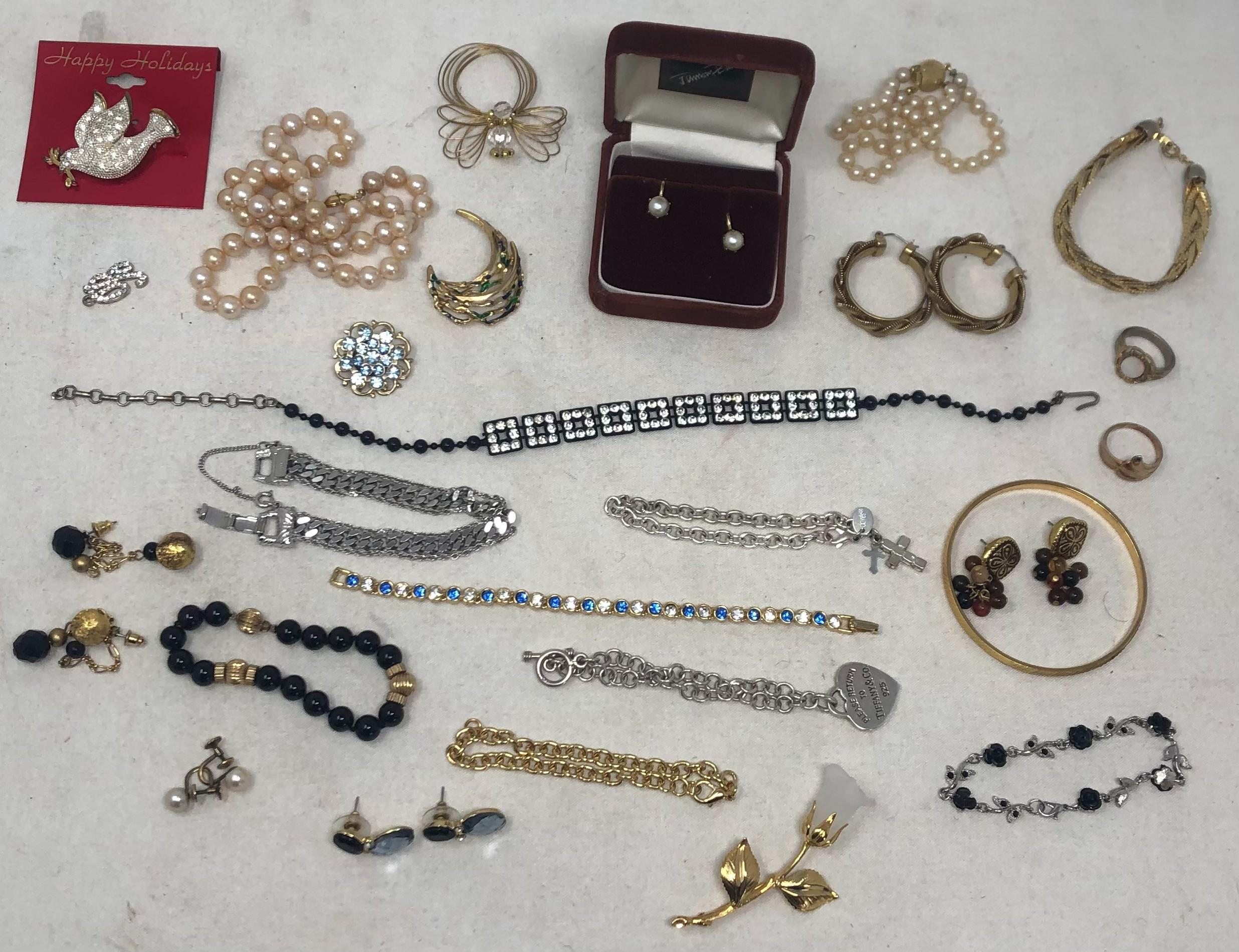 """Collection of dressy costume jewelry includes Tiffany and Monet: eight bracelets include sterling silver Tiffany bracelet with heart shaped pendant marked """"Please return to Tiffany & Co., 925"""", blue and white crystal ..."""