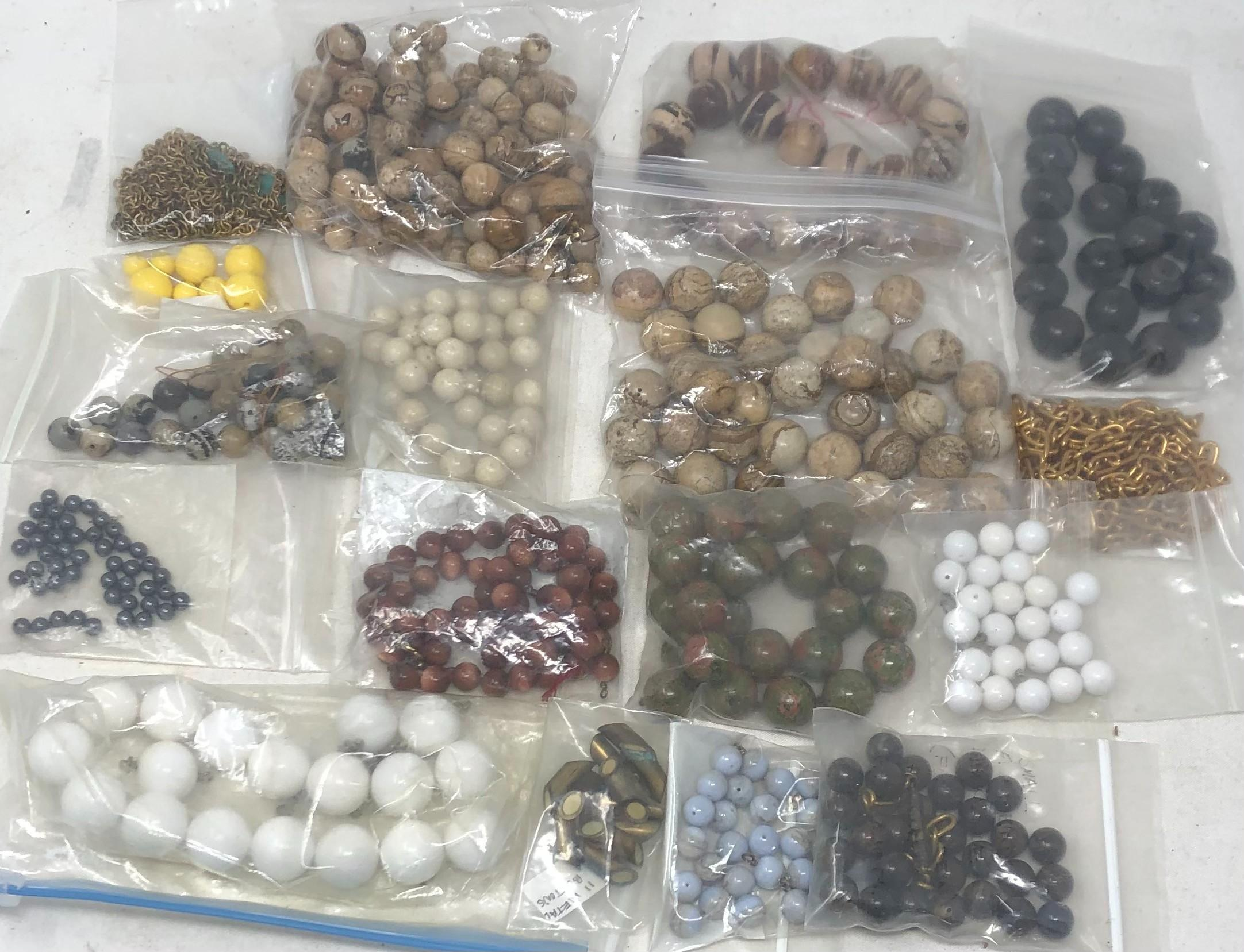 Fifteen bags of beads: white, metal, yellow, large brown, light blue, multi-color, black metal, cream color, green and red multi, tan multi color ceramic, one long brass chain, 60 inches, small bag partial chains with...