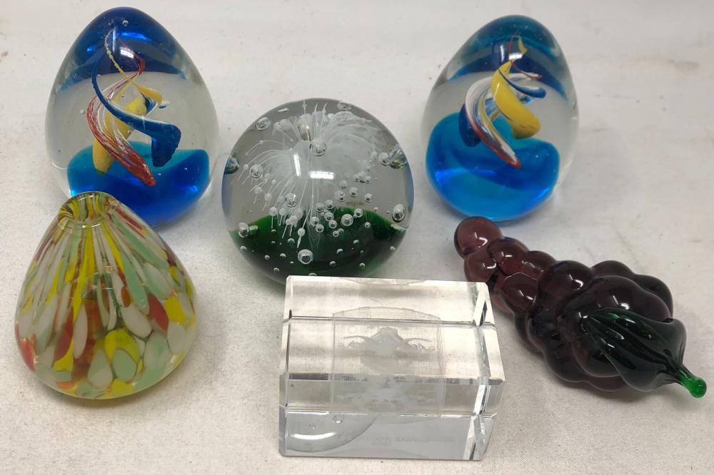 Five art glass paperweights and a small art glass vase.