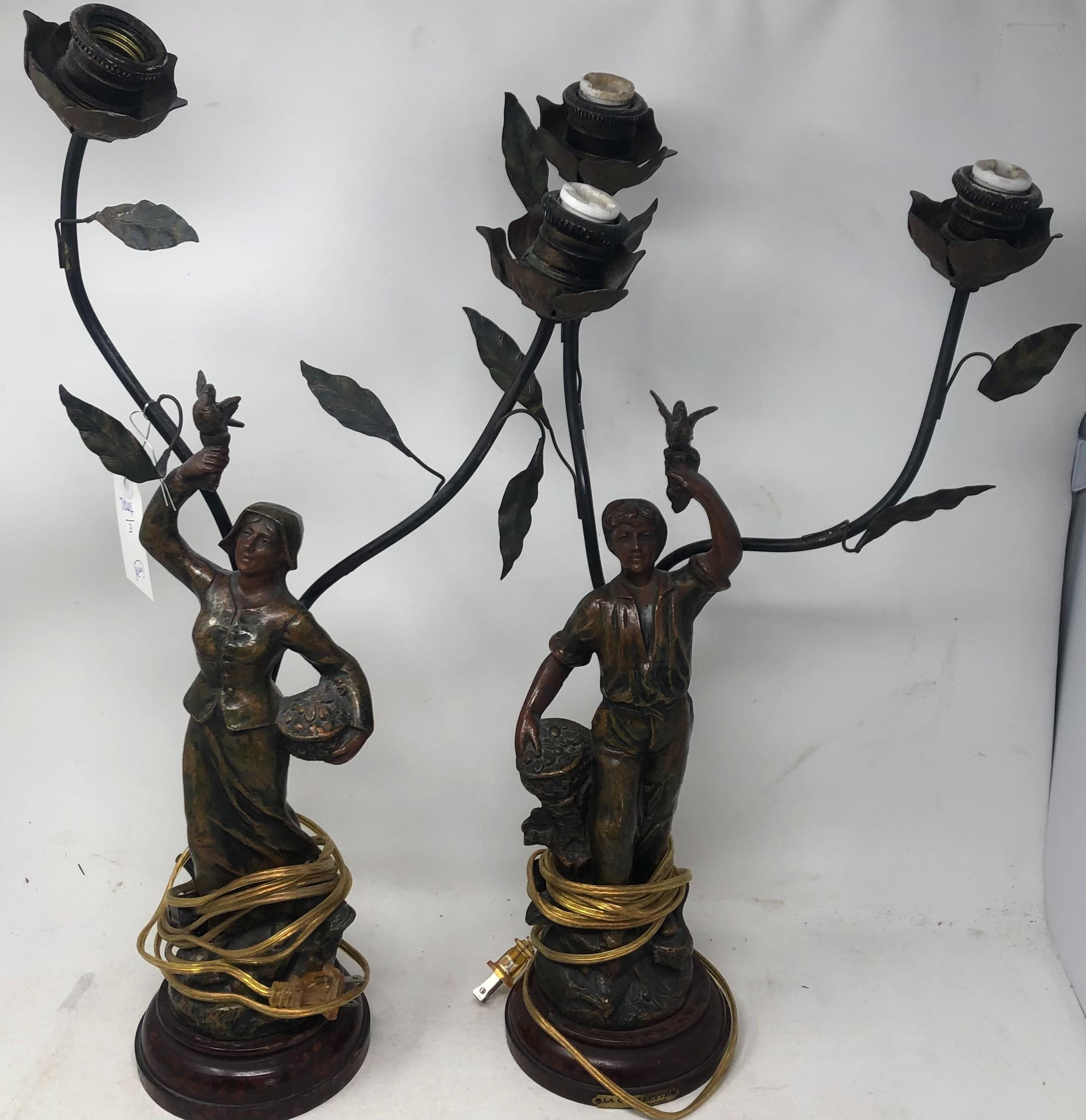 Pair of Art Nouveau style metal table lamps featuring a man and woman, each holding a bird.