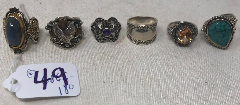 Six lady's sterling silver rings; one 12K GF depicting feather and shield, size 8 3/4; unmarked band with border design, size 7 3/4; sterling reticulated with peach tone glass stone, size 6 1/4; sterling with teardrop...