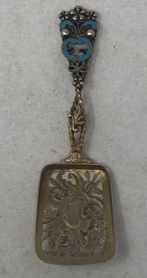 """A Sterling and Enamel Mint/Nut Spoon. The handle with applied flowers and leaves, with enamel highlighting. The bowl reticulated with a light gold wash. Marked Sterling, .455 troy ounces, 4.25"""" in length"""