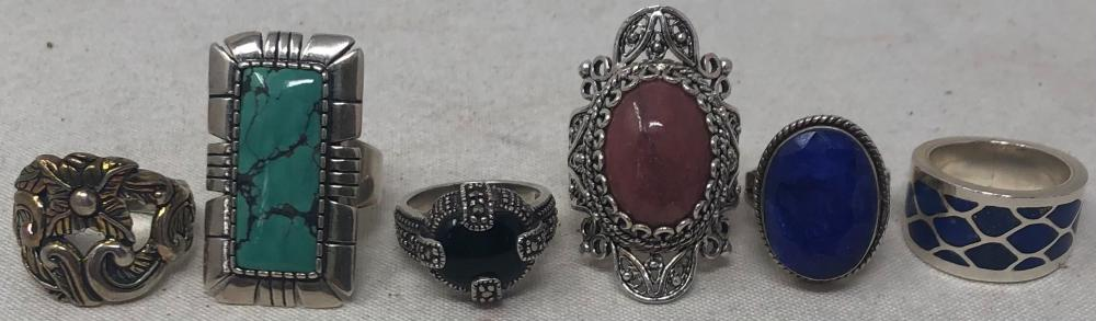 Six sterling silver lady's rings: one with blue glass stone, size 4 1/2; carved with deep green stone, size 5 1/2; sterling and lapis band, size 5 3/4; large reticulated mount with rose color stone, size 8; sterling o...