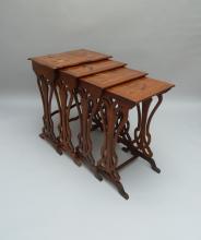 Émile GALLÉ (1846-1904)   Suite de quatre tables gigognes en noyer, piétement en volutes végétales, entretoises à hauteurs différentes, plateaux à décors marquetés de fleurs en bois exotiques.