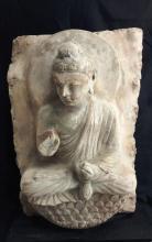 Buddha Maïtreya assis sur un lotus vêtu de la robe monastique utarasanga aux plissés hellénistiques, une main en abyamudra et l'autre tenant une offrande.