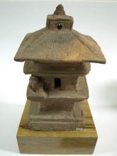 Modèle de temple miniature habité de figures en méditation.