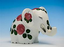 A Wemyss Plichta elephant in red clover pattern, eyes closed with long lashes, 8in. (20.3cm.) from trunk tip to tail,