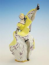 A Limoges figure of a can-can girl in canary yellow dress and hat, in the port d'armes position revealing her layered petticoats,