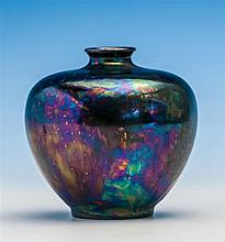 A Ruskin iridescent vase of squat ovoid form, short flared neck, supported on raised circular foot,
