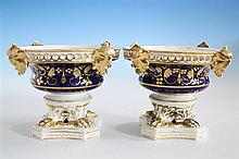 A pair of Derby porcelain shallow urn shaped pot pourris early 19th century, the pierced rims with four gilded, leafy masks,