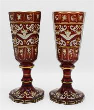 A pair of 19th century Bohemian enamelled ruby glass goblets the ten sided panel cut flared bowls finely decorated with winged masks,