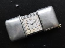 A Movado travel or purse clock 1920s-30s, the white metal rectangular case with diamond engraving, square dial with Arabic numerals,