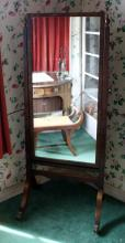 A Victorian mahogany cheval mirror the rectangular plate between flared square upright supports with urn finials,