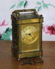 A late 19th century French brass carriage clock the circular dial with engine turned sun burst design to centre,