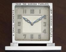 A clock with 8th Gurkha Rifles and military interest the chrome Art Deco clock of square form on rectangular base,