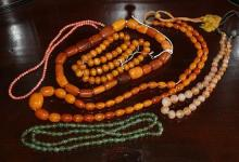 A group of assorted necklaces comprising three with amber beads, one spinach jade,