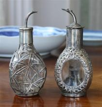 Two Oriental silver mounted glass oil bottles 1920s-30s, the moulded three-sided clear glass bodies with pierced silver mounts,