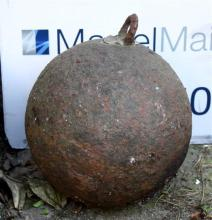 A large 18th century iron cannonball, with later soldered loop to top. 7.75in. (19.75cm.) diameter.