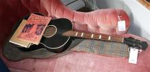 An ebonised four string acoustic guitar