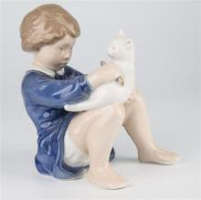 A Royal Copenhagen figure of a girl brushing a cat c.1975-1979, no.4631, designed by John Calster, 6in. (15.2cm.) high.