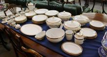 A Limoges porcelain dinner service gilt wheat sheaf and burgundy border.
