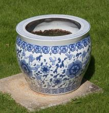 A blue and white jardiniere of ovoid form with flattened rim and Greek key design border, with flowering peony and prunus decoration,