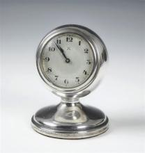 A George V silver desk clock the silvered Arabic dial within a circular case on flared pedestal base, Chester 1928,
