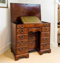 A George III mahogany kneehole desk with lifting top the unusual lifting moulded edged top revealing centralised green and gilt tool...