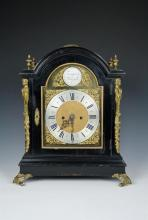 A 19th century ebonised bracket clock with gilt brass caryatid mounts, finials and feet, carrying handle to top of case,