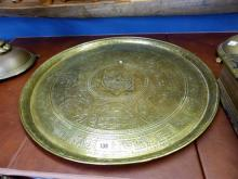 An Arabian brass feast platter late 18th / early 19th century, the centre decorated with calligraphic circular design within a star,