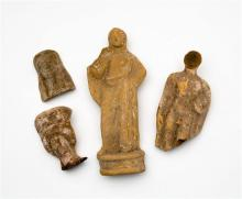 A large Greek buff terracotta votive figure depicting a standing robed goddess, on channelled demi lune base,