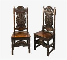 A pair of 17th century carved oak side chairs the arched foliate and scroll carved top rails over S-scroll and foliate carved splats,