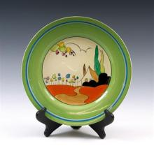 A Clarice Cliff Tulips pattern circular plate circa 1934, hand painted with stylized cottage landscape on honeyglaze, green,