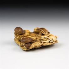 A Japanese carved ivory netsuke Meiji period (1868-1912), with three leverets playing amongst toadstools,