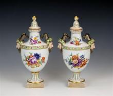 A pair of covered Dresden twin handled vases c.1900, of urn form, decorated with floral sprays and fruiting vine borders,
