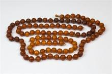 Two amber bead necklaces early 20th century, both with circular, 13mm. evenly sized beads,