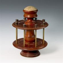 A 19th century treen cotton reel stand of circular design, having eight cotton reel holding rods, surmounted by a pin cushion.