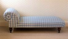 A Victorian day bed the scroll bolster and stuffover seat reupholstered in blue check,