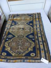 A small Kuba rug early 20th century, the row of three joined octagonal medallions in buff, light brown, blue,