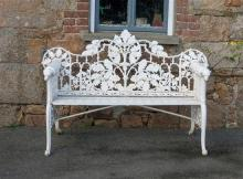 A Victorian white painted cast iron garden bench the shaped openwork back with entwined oak leaf and acorn decoration,