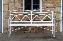 A Victorian painted wrought iron garden bench the reeded openwork frame with double ellipse toprail over an arched trellis back,