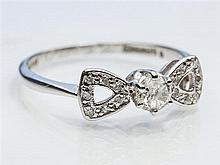 An 18ct white gold and diamond ring 1940s, in the form of a bow set with fourteen tiny round cut diamonds,