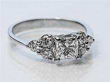 An 18ct white gold and seven stone diamond ring the centre 0.618 carat VS2/G Princess cut diamond, with EGL Certificate,