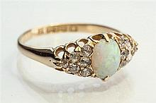 An Edwardian 18ct yellow gold, opal and diamond ring c.1909, the oval white opal flanked by twelve small old cut diamonds, ring size P.