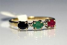 A 9ct gold, three colour stone and diamond ring the three oval cut stones comprising a ruby, emerald and sapphire,