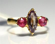 A gold, topaz and ruby ring the central marquise cut topaz flanked by round cut rubies, ring size J½.