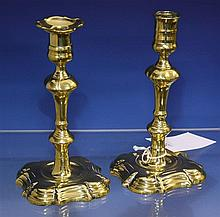 A matched pair of George I seamed brass silver form candlesticks the double knopped stems with peened in lower sections and ringed n...