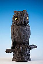 A large late 19th century Irish carved bog oak owl inkwell with hinged head with painted glass eyes,