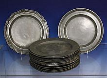 A collection of antique pewter plates with plain and silver rims, some with touch marks and engraved initials,