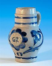 An 18th century German Westerwald stoneware ale jug of bellied form with cylindrical ring turned neck and loop handle,